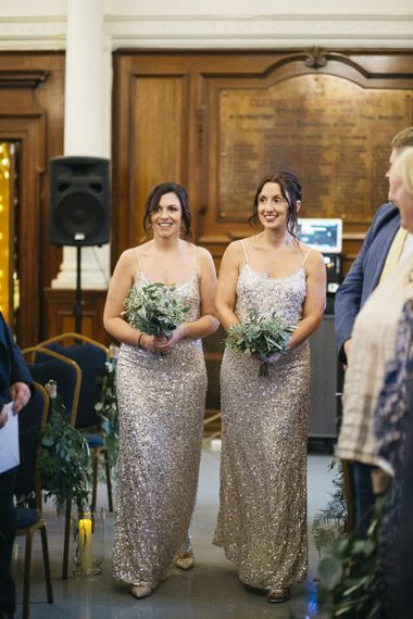 Bridesmaids wearing beautiful embellished dresses and clutching simple white foliage bouquets