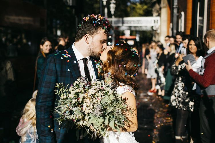 Bride and groom confetti shot at autumn celebration in London with green and white foliage bouquet