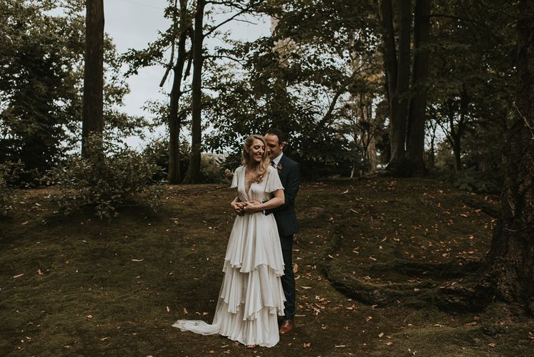 Bride in Tiered Houghton NYC Wedding Dress and Groom in Check House of Fraser Suit Cuddling in a Forest