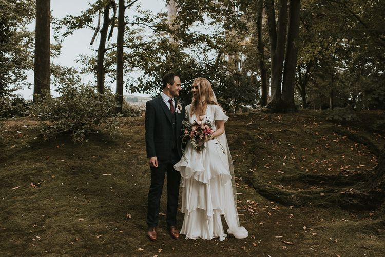 Bride in Tiered Houghton NYC Wedding Dress and Groom in Check House of Fraser Suit in a Forest