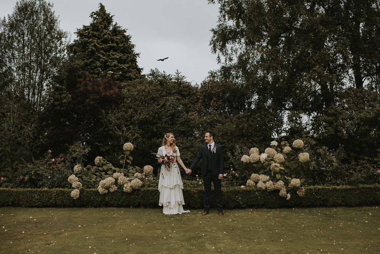 Bride in Tiered Houghton NYC Wedding Dress and Groom in Check House of Fraser Suit Holding Hands in the Garden