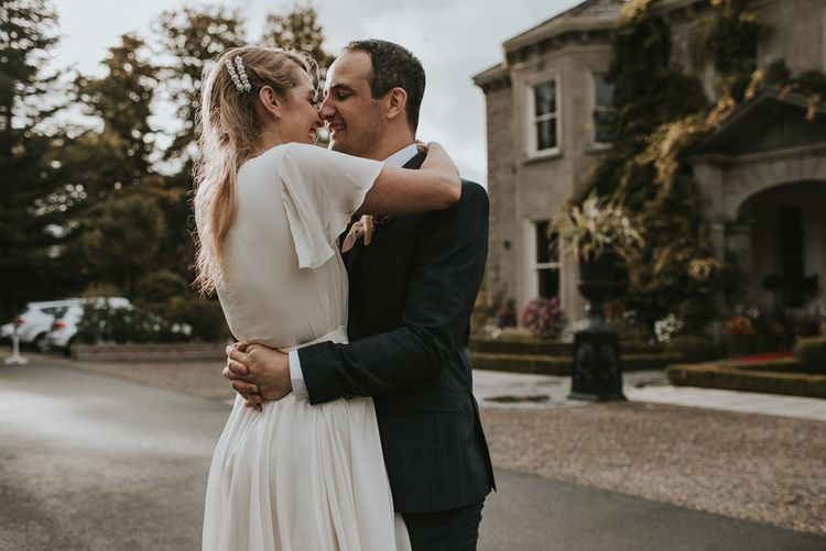 Bride in Tiered Houghton NYC Wedding Dress and Groom in Check House of Fraser Suit  Embracing