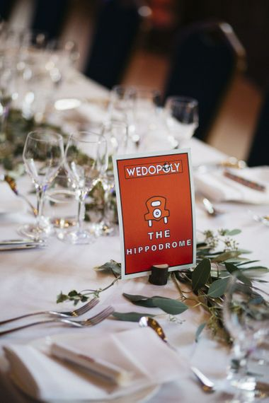 Monopoly style table setting names for London reception with foliage decor