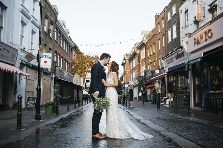 Bride and groom at London wedding with white foliage bouquet