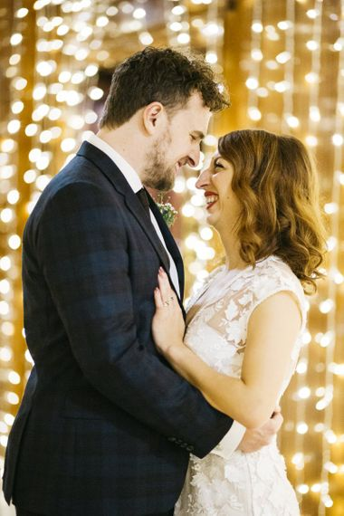 Bride and groom embrace with fairy-light backdrop