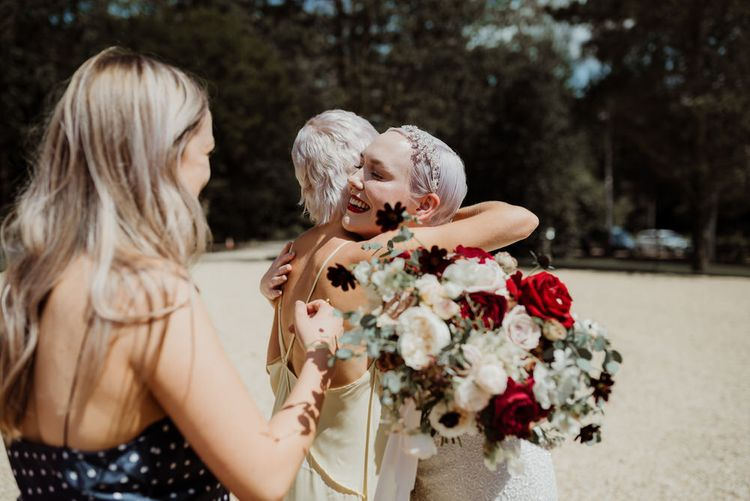 Bride with White and Red Rose Bouquet Receiving Hugs From Wedding Guests
