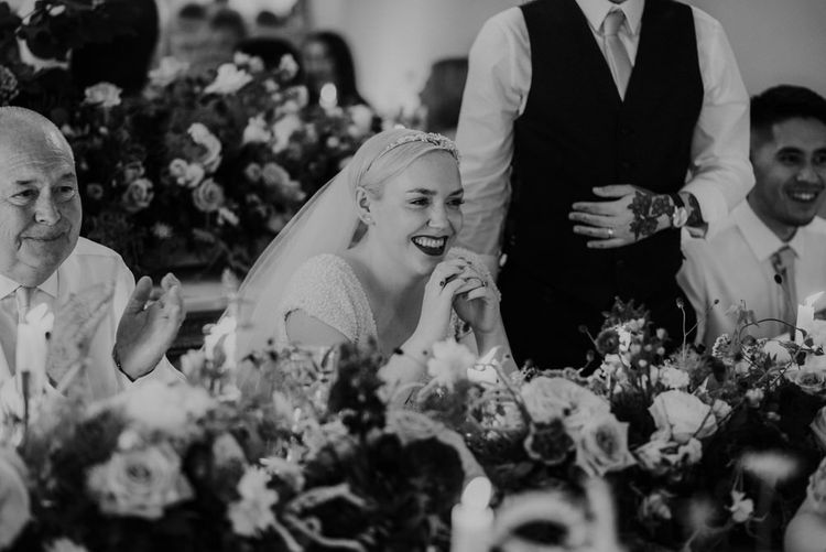 Bride with Short Hair and Red Lipstick Laughing During Wedding Reception Speeches