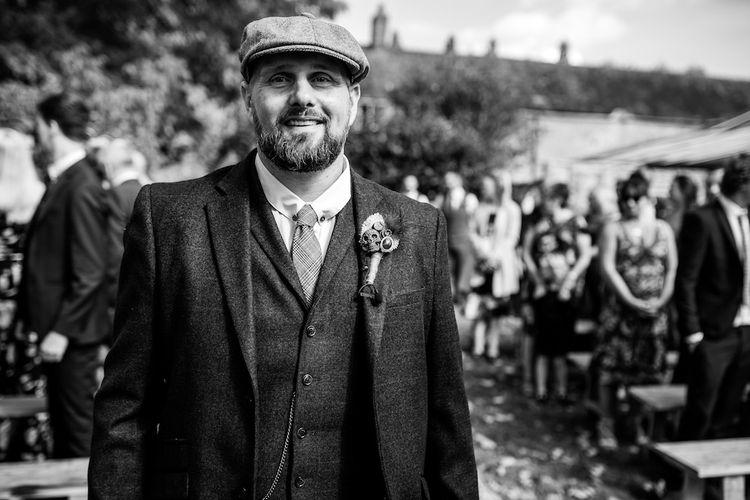 Wedding Ceremony | Groom in Burgundy Tweed Three Piece Suit | Edison Bulb Floral Installation at Kingsthorpe Lodge Barn Wedding | Johnny Dent Photography