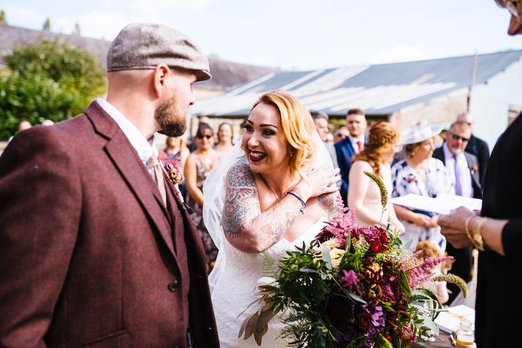 Wedding Ceremony | Bride in Strapless Sassi Holford Wedding Dress with Sweetheart Neckline | Groom in Burgundy Tweed Three Piece Suit | Bright Bouquet | Edison Bulb Floral Installation at Kingsthorpe Lodge Barn Wedding | Johnny Dent Photography