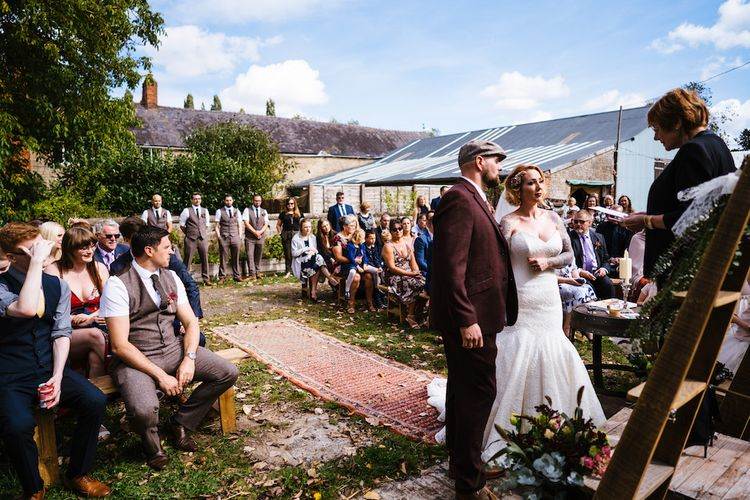 Wedding Ceremony | Bride in Strapless Sassi Holford Wedding Dress with Sweetheart Neckline | Groom in Burgundy Tweed Three Piece Suit | Edison Bulb Floral Installation at Kingsthorpe Lodge Barn Wedding | Johnny Dent Photography