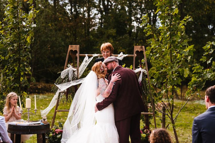 Wedding Ceremony | First Kiss | Bride in Strapless Sassi Holford Wedding Dress with Sweetheart Neckline | Groom in Burgundy Tweed Three Piece Suit | Edison Bulb Floral Installation at Kingsthorpe Lodge Barn Wedding | Johnny Dent Photography