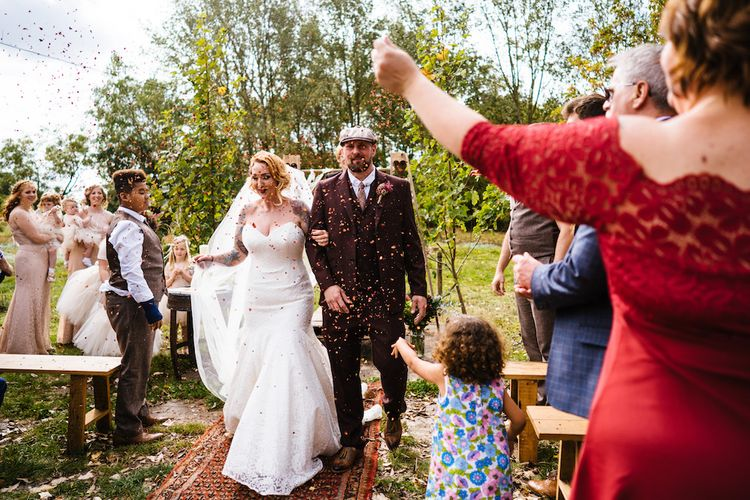 Confetti Moment | Bride in Strapless Sassi Holford Wedding Dress with Sweetheart Neckline | Groom in Burgundy Tweed Three Piece Suit | Edison Bulb Floral Installation at Kingsthorpe Lodge Barn Wedding | Johnny Dent Photography
