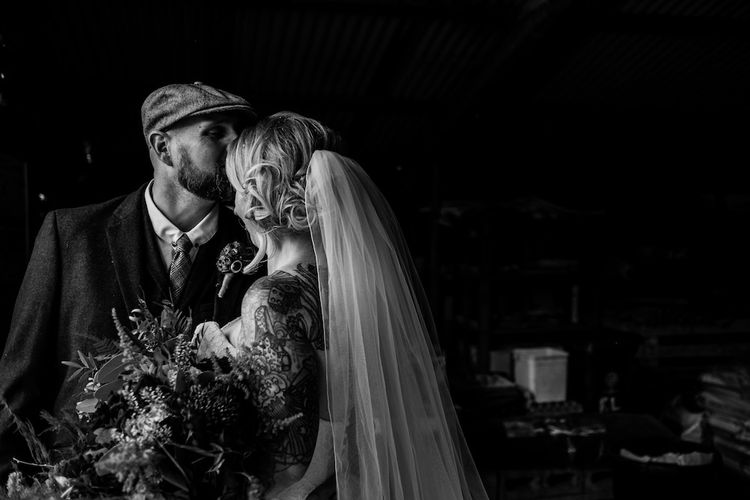 Bride in Strapless Sassi Holford Wedding Dress with Sweetheart Neckline | Groom in Burgundy Tweed Three Piece Suit | Edison Bulb Floral Installation at Kingsthorpe Lodge Barn Wedding | Johnny Dent Photography