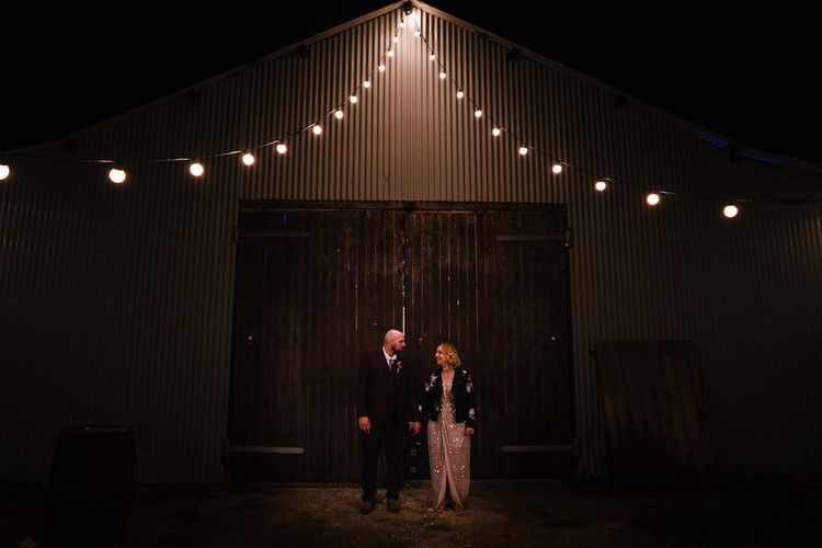 Bride in Sequinned Kimono from ASOS | Groom in Burgundy Tweed Three Piece Suit | Edison Bulb Floral Installation at Kingsthorpe Lodge Barn Wedding | Johnny Dent Photography