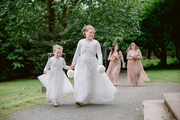 Flower girls and bridesmaids make their way to wedding ceremony
