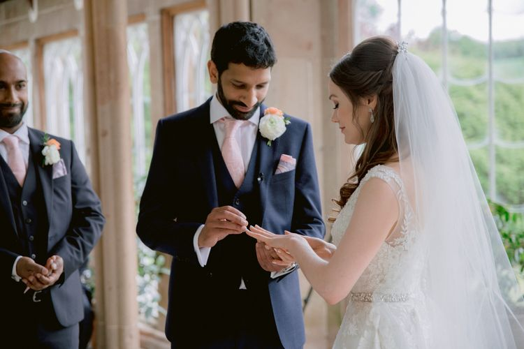 Bride and groom exchange rings during ceremony
