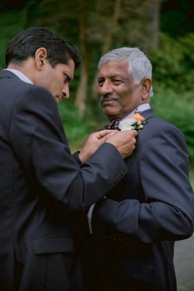 Groom fits father with bright floral buttonhole