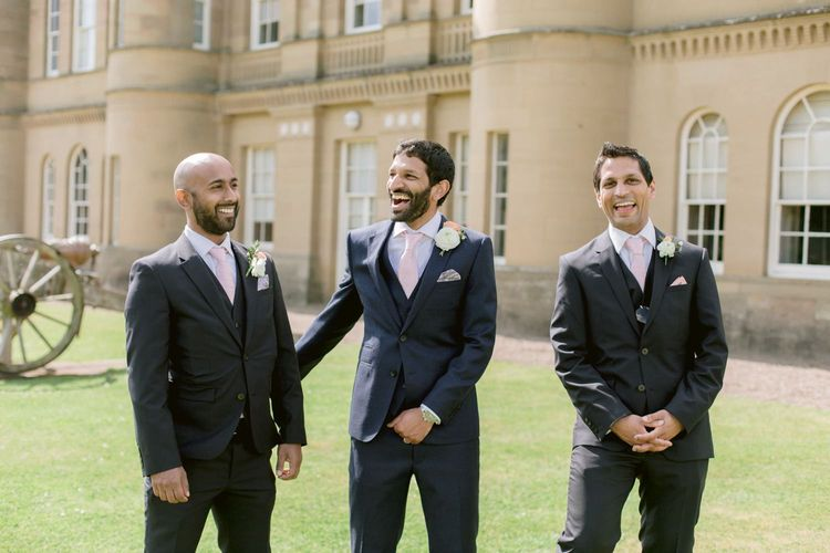 Groomsmen in matching suits with pink ties