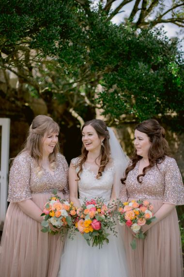 Pink bridesmaid dresses with bright peony bouquets