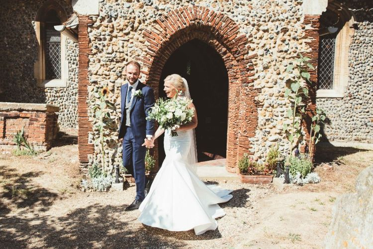 Just Married   Bride in Essense of Australia Dress with Spaghetti Straps and Fishtail   Floor Length Veil   Bridal Bouquet of White Flowers and Greenery   Groom in Blue Suit with White and Green Buttonhole   Quintessential English Country Wedding in Glass Marquee at Family Home   Maryanne Weddings Photography