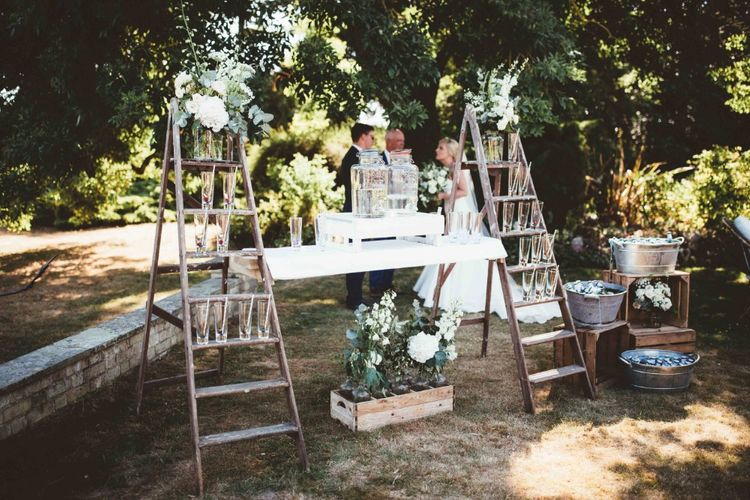 Drinks Station with Rustic Ladders   Kilner Jars   Beer Troughs   White Flowers and Greenery   Quintessential English Country Wedding in Glass Marquee at Family Home   Maryanne Weddings Photography