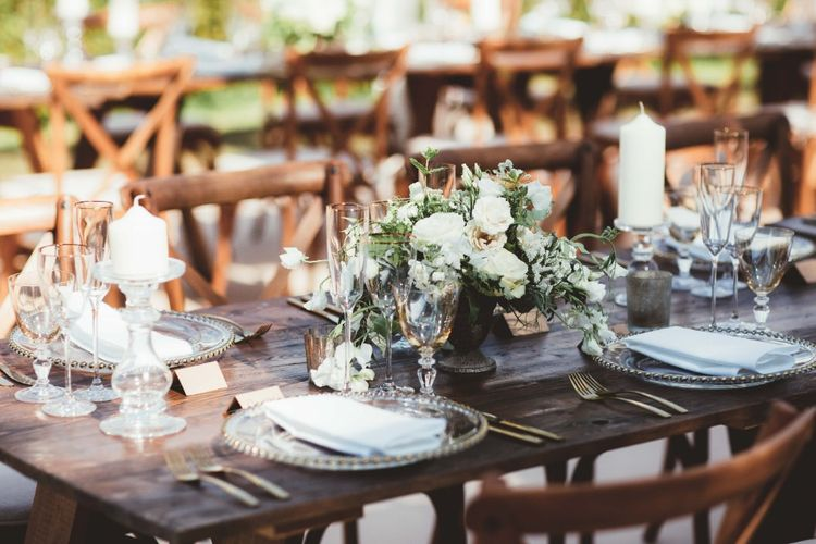 Long Wooden Farm Table   Wooden Cross Back Chairs   Glass Charger Plates   Gold Cutlery   Gold Rimmed Glassware   Table Centrepieces of White Flowers and Greenery   White Pillar Candles   Quintessential English Country Wedding in Glass Marquee at Family Home   Maryanne Weddings Photography