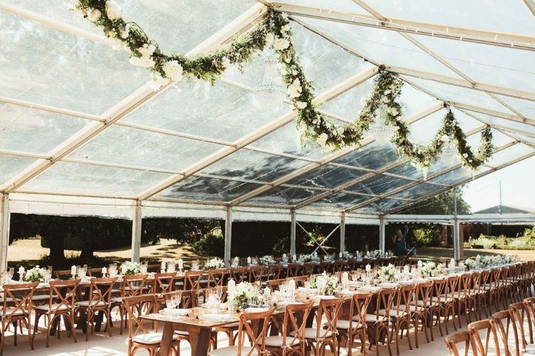 Glass Marquee   Hanging Garland with White Flowers and Greenery   Long Wooden Farm Tables   Wooden Cross Back Chairs   Glass Charger Plates   Gold Cutlery   Gold Rimmed Glassware   White Pillar Candles   Glass Candlesticks   Quintessential English Country Wedding in Glass Marquee at Family Home   Maryanne Weddings Photography