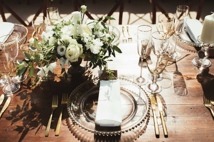 Place Setting   Glass Charger Plate   Gold Cutlery   Gold Rimmed Glassware   Table Arrangement of White Flowers and Greenery   Quintessential English Country Wedding in Glass Marquee at Family Home   Maryanne Weddings Photography