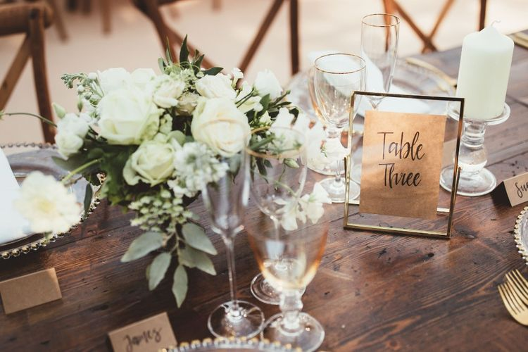 Table Number in Gold Frame   Gold Cutlery   Gold Rimmed Glassware   Table Arrangement of White Flowers and Greenery   Quintessential English Country Wedding in Glass Marquee at Family Home   Maryanne Weddings Photography