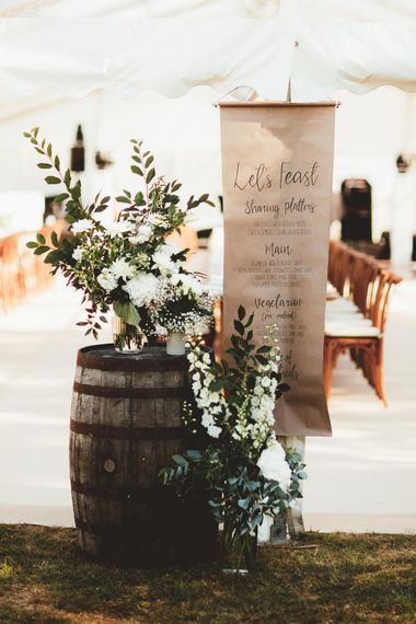 Wedding Breakfast Menu in Calligraphy on Kraft Paper   Wooden Barrel   Large Glass Vases  of White Flowers and Eucalyptus   Quintessential English Country Wedding in Glass Marquee at Family Home   Maryanne Weddings Photography