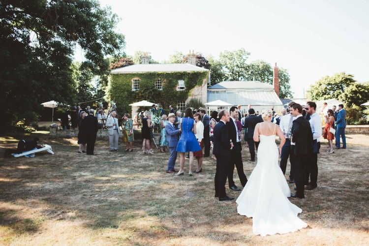 Wedding Reception   Drinks in the Garden   Bride in Essense of Australia Dress with Spaghetti Straps and Fishtail   Quintessential English Country Wedding in Glass Marquee at Family Home   Maryanne Weddings Photography