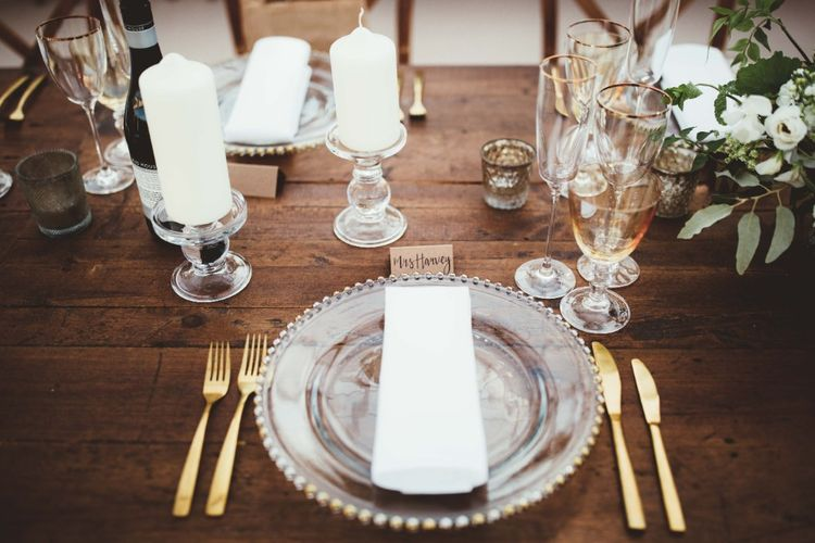 Place Setting   Glass Charger Plates   Gold Cutlery   Gold Rimmed Glassware   White Pillar Candles   Glass Candlesticks   Calligraphy Name Cards   Quintessential English Country Wedding in Glass Marquee at Family Home   Maryanne Weddings Photography