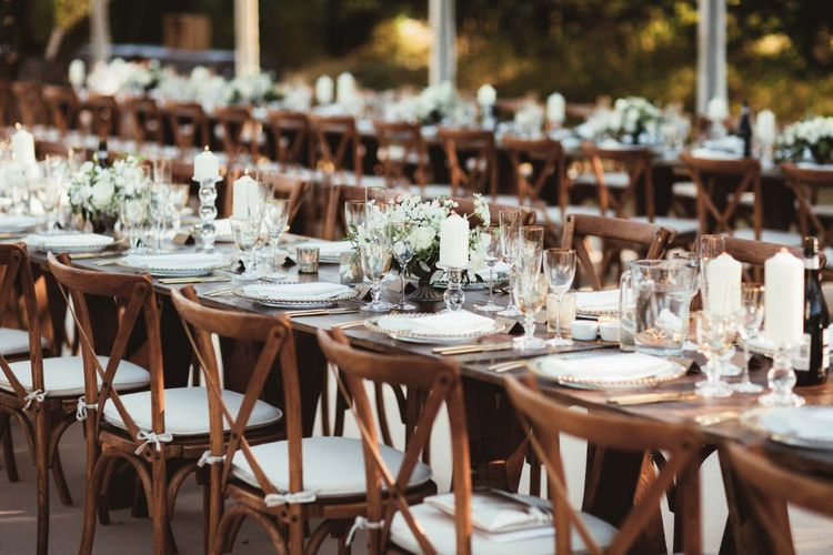 Long Wooden Farm Tables   Wooden Cross Back Chairs   Glass Charger Plates   Gold Cutlery   Gold Rimmed Glassware   White Pillar Candles   Glass Candlesticks   Table Arrangements of White Flowers and Greenery   Quintessential English Country Wedding in Glass Marquee at Family Home   Maryanne Weddings Photography