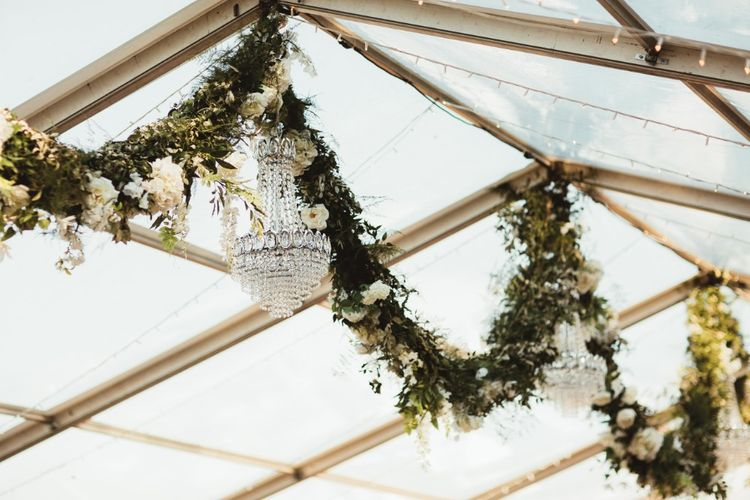 Glass Marquee   Hanging Garland with White Flowers and Greenery   Glass Chandeliers   Fairy Lights   Quintessential English Country Wedding in Glass Marquee at Family Home   Maryanne Weddings Photography