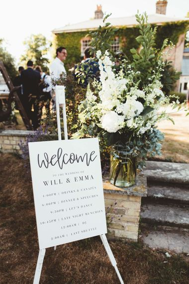 Welcome Sign   Glass Vase with White Flowers and Greenery   Quintessential English Country Wedding in Glass Marquee at Family Home   Maryanne Weddings Photography