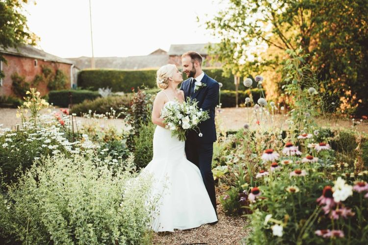Bride in Essense of Australia Dress with Spaghetti Straps and Fishtail   Groom in Blue Suit with White and Green Buttonhole   Bridal Bouquet of White Flowers and Greenery   Quintessential English Country Wedding in Glass Marquee at Family Home   Maryanne Weddings Photography
