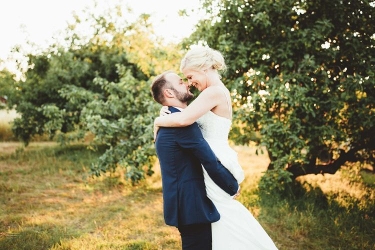 Bride in Essense of Australia Dress with Spaghetti Straps and Fishtail   Groom in Blue Suit with White and Green Buttonhole   Quintessential English Country Wedding in Glass Marquee at Family Home   Maryanne Weddings Photography