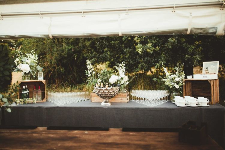 Wedding Reception Drinks Table   Wooden Crates   Large Floral Displays   Quintessential English Country Wedding in Glass Marquee at Family Home   Maryanne Weddings Photography
