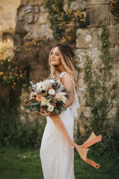 Boho Bride with Half Up Half Down Braided Hair Holding a Bouquet with Pampas Grass and Coral Flowers Tied in Ribbon