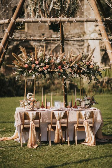 Outdoor Tablescape with Floral Installation Under a Naked Tipi