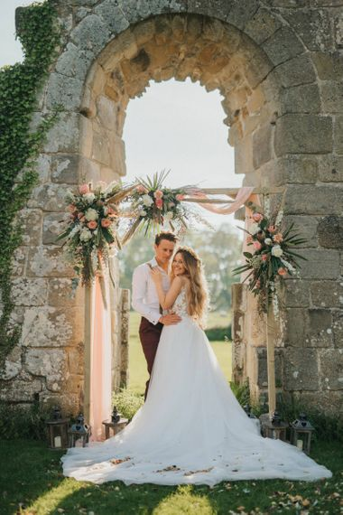 Boho Bride and Groom Standing in Front of a Wooden Altar Covered in Flowers