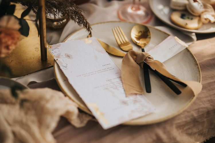 Place Setting with Gold and Black Cutlery Tied with Ribbon and Menu Cards