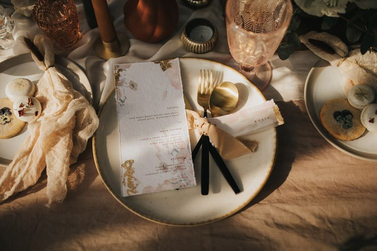 Elegant Place Setting with Gold and Black Cutlery Tied with Ribbon and Menu Cards