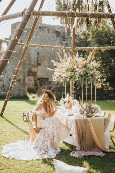 Boho Bride with Straw Hat Sitting at a Tablescape  with Floral Installation Under a Naked Tipi