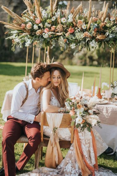 Boho Bride in Lace Wedding Dress and Fedora Hat and Groom in Braces Sitting at Outdoor Tablescape