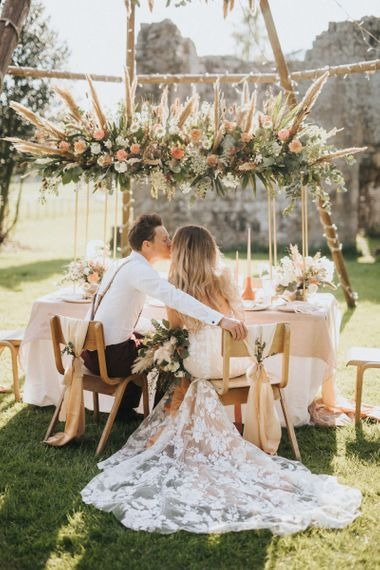 Boho Bride and Groom Kissing at Their Tablescape Under a Naked Tipi