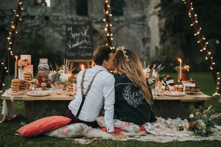 Boho Bride in Customised Leather Jacket and Groom in Braces Kissing at Candlelit Dessert Table