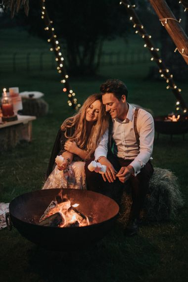 Boho Bride and Groom Embracing a Smoke Pit Toasting Marshmallows