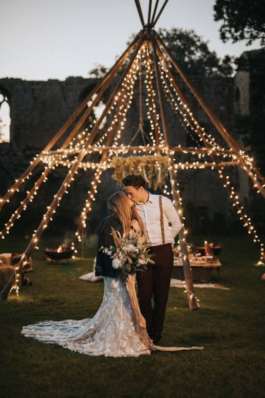 Boho Bride and Groom Standing in Front of Light Covered Naked Tipi