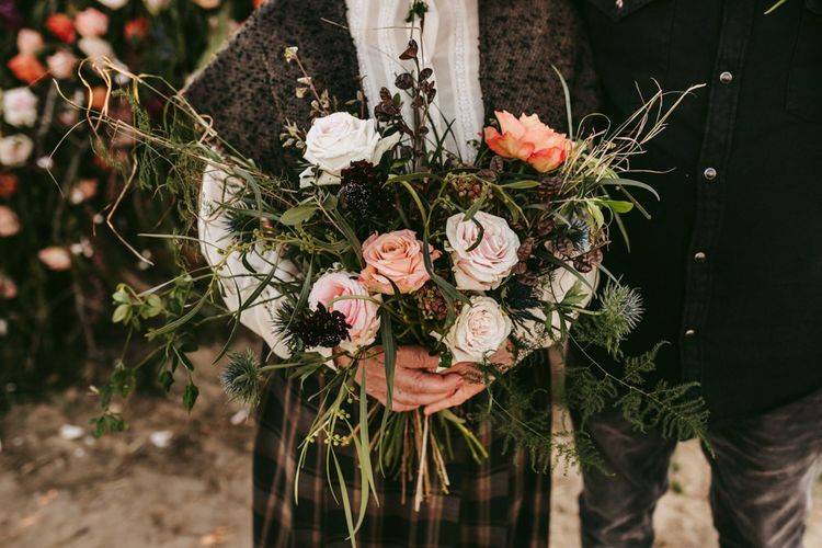Wild wedding bouquet with roses and foliage